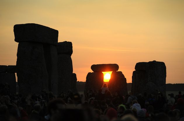 The sun rising behind the stones at