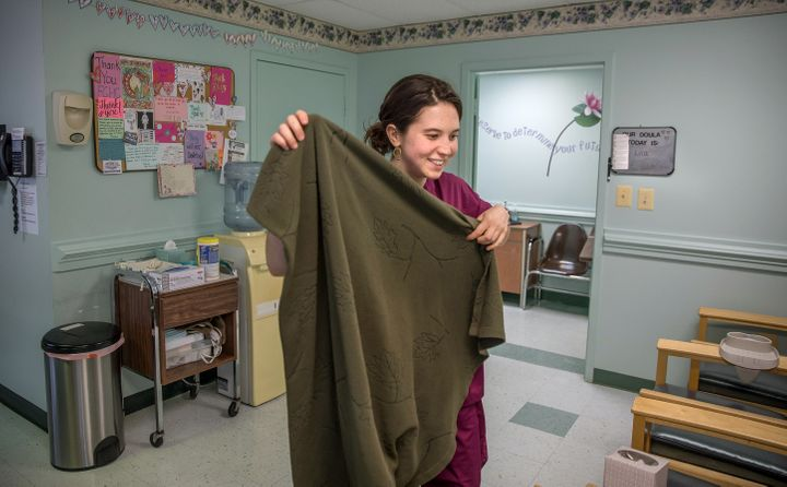 Lila, an abortion doula, gets a blanket for a patient in the recovery room at a Virginia abortion and family planning clinic