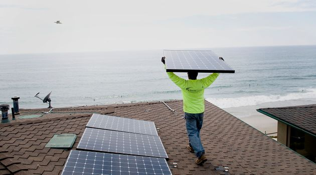 Andres Quiroz, an installer for Stellar Solar, carries a solar panel during installation at a home in...
