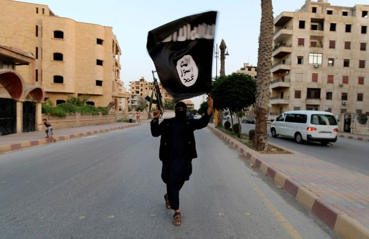 A member of the self-described Islamic State in Iraq and the Levant waves a flag in Raqqa, Syria, on June 29, 2014.