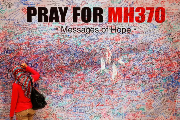 A woman leaves a message of support and hope for the passengers of missing Malaysia Airlines flight Mh370...