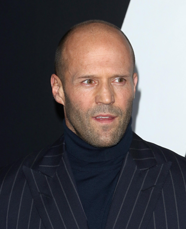 Jason Statham's short hair fades into his receding hairline.
