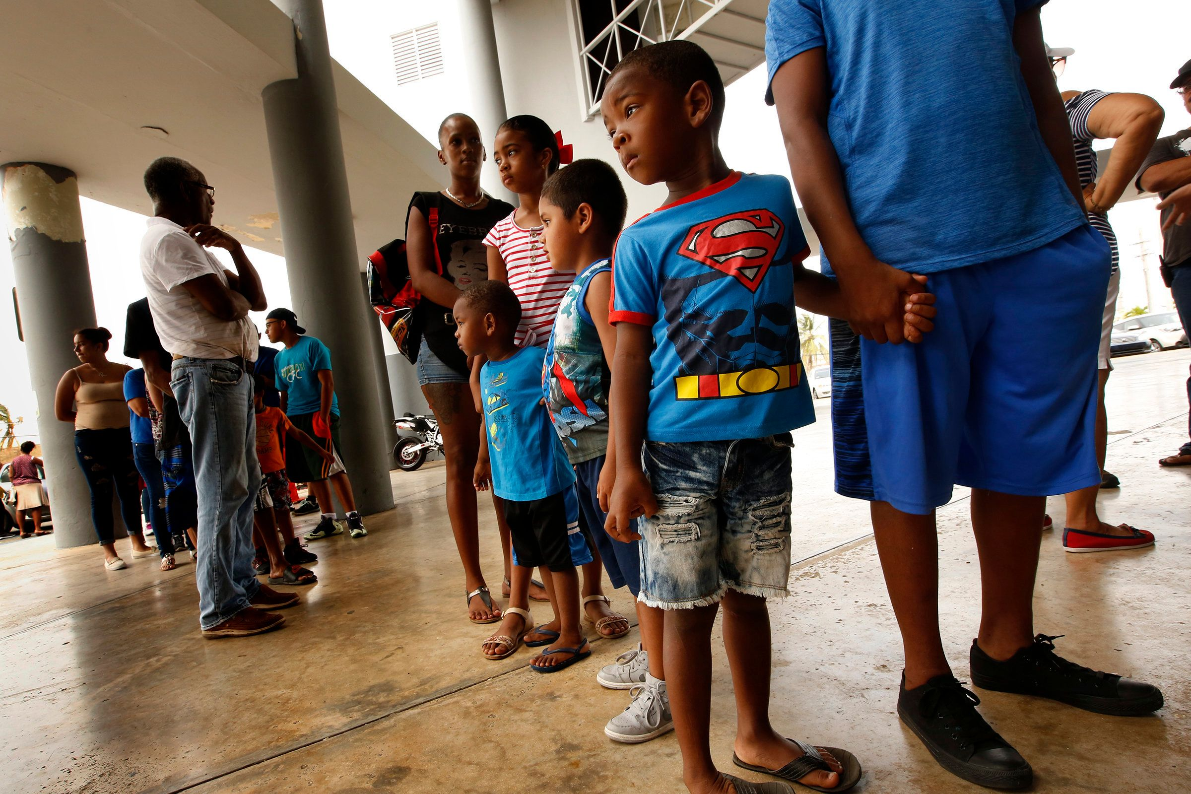 RIO GRANDE, PUERTO RICO - SEPTEMBER 27, 2017: Members of the Pisaro family of four children, wait in line for FEMA food distribution in the town of Rio Grande. The food only started today, one week after Hurricane Maria. In The northeast section of Puerto Rico, town of Rio Grande, people are only now starting to receive aid of any kind and many don't even know it's available. (Photo by Carolyn Cole/Los Angeles Times via Getty Images)