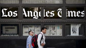 People walk past the building of Los Angeles Times newspaper, which is owned by Tribune Publishing Co, in Los Angeles, California, U.S., April 27, 2016. REUTERS/Lucy Nicholson