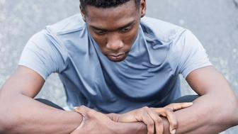 Close-up of a serious young African American man sitting on the pavement. He is an athlete wearing sports clothing, in deep thought, looking down with a serious, sad expression.