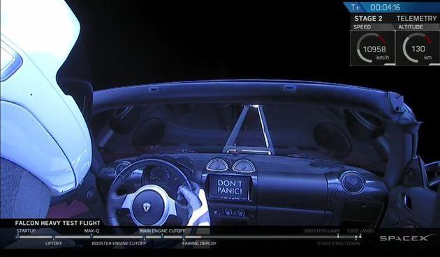 """팰컨 헤비에 실린 테슬라 전기차 로드스터. 대시보드에 """"당황하지 마라""""는 문구가 보인다. 운전대를 잡고 있는 건"""
