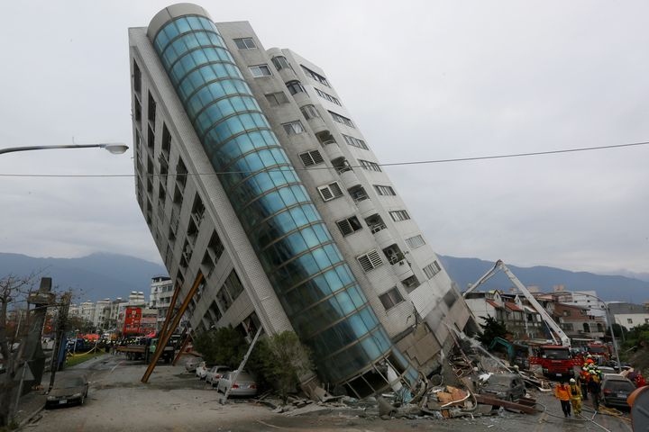 Rescue workers are seen by a damaged building after an earthquake hit Hualien, Taiwan February 7, 2018.