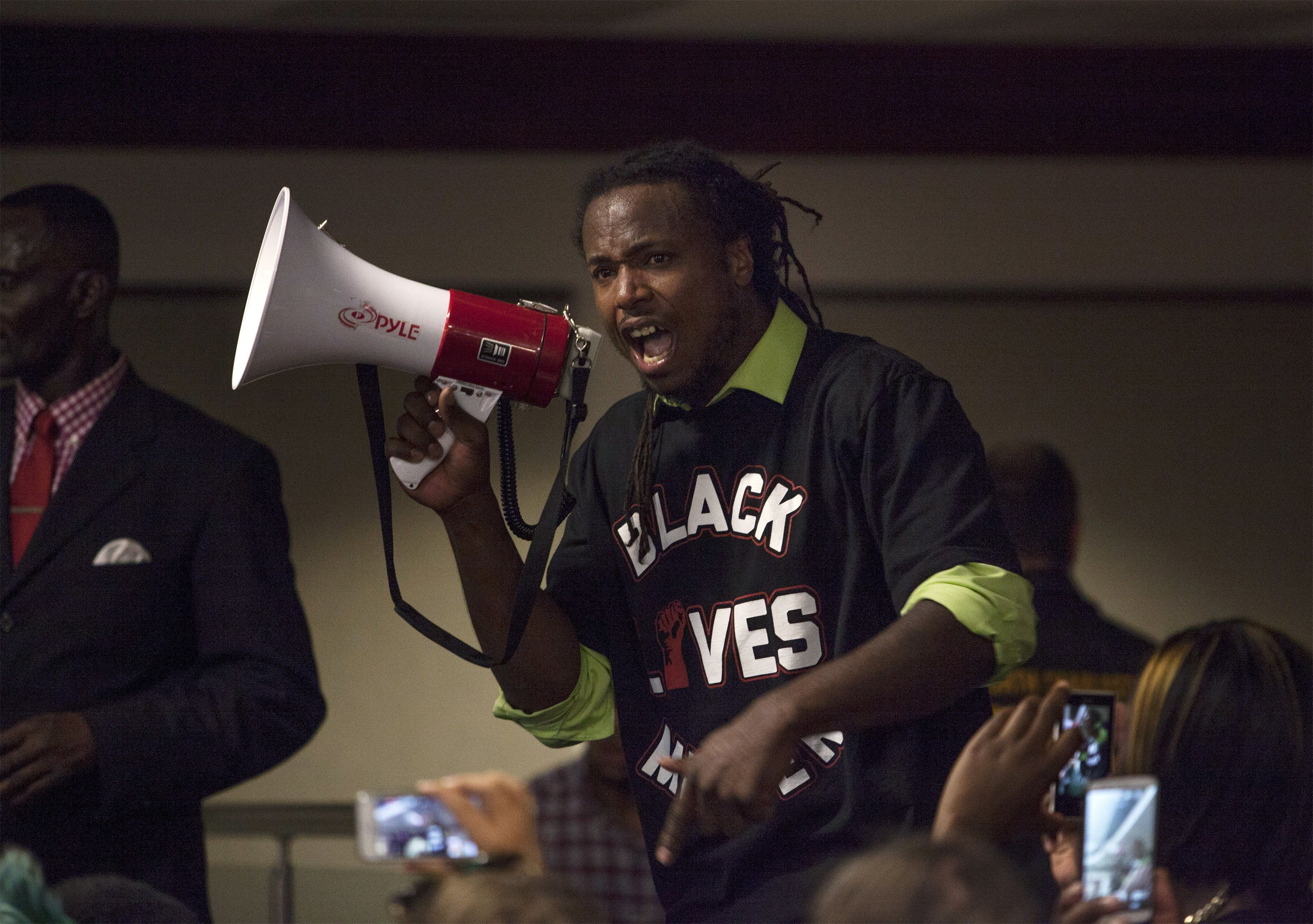Muhiydin Moye D'Baha of the Black Lives Matter movement, uses a bull horn to make a point during a news conference with North Charleston Police and Government officials in North Charleston, South Carolina April 8, 2015. Demonstrators rallied on Wednesday against what they described as a culture of police brutality in South Carolina in the case of white officer Michael Slager, who was caught on video killing 50-year-old Walter Scott, a black man, by shooting him in the back as Scott ran away after a traffic stop. Slager was charged on Tuesday with murder in the death of Scott.   REUTERS/Randall Hill