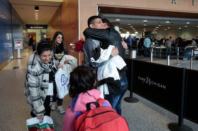 Rami Al-Qassab, at right, hugs his brother after being reunited with his Iraqi refugee mother Amira,...