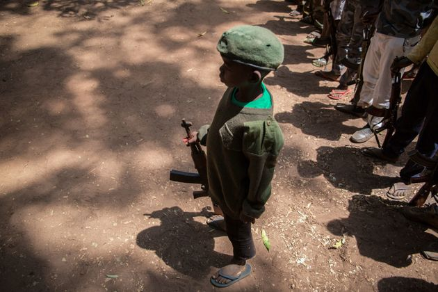 A newly-released child soldier stands with his rifle during a ceremony on Feb. 7,