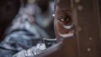 A newly released child soldier looks through a rifle trigger guard during a release ceremony for child soldiers in Yambio, South Sudan, on February 7, 2018. More than 300 child soldiers, including 87 girls, have been released in South Sudan's war-torn region of Yambio under a programme to help reintegrate them into society, the UN said on on Februar y 7, 2018. A conflict erupted in South Sudan little more than two years after gained independence from Sudan in 2011, causing tens of thousands of deaths and uprooting nearly four million people. The integration programme in Yambio, which is located in the south of the country, aims at helping 700 child soldiers return to normal life. / AFP PHOTO / Stefanie Glinski        (Photo credit should read STEFANIE GLINSKI/AFP/Getty Images)
