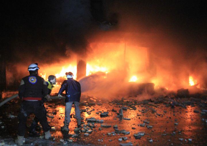 Civil defense members extinguish a fire that broke out after Russian airstrikes hit Idlib's Maarrat al-Numan district in Syri