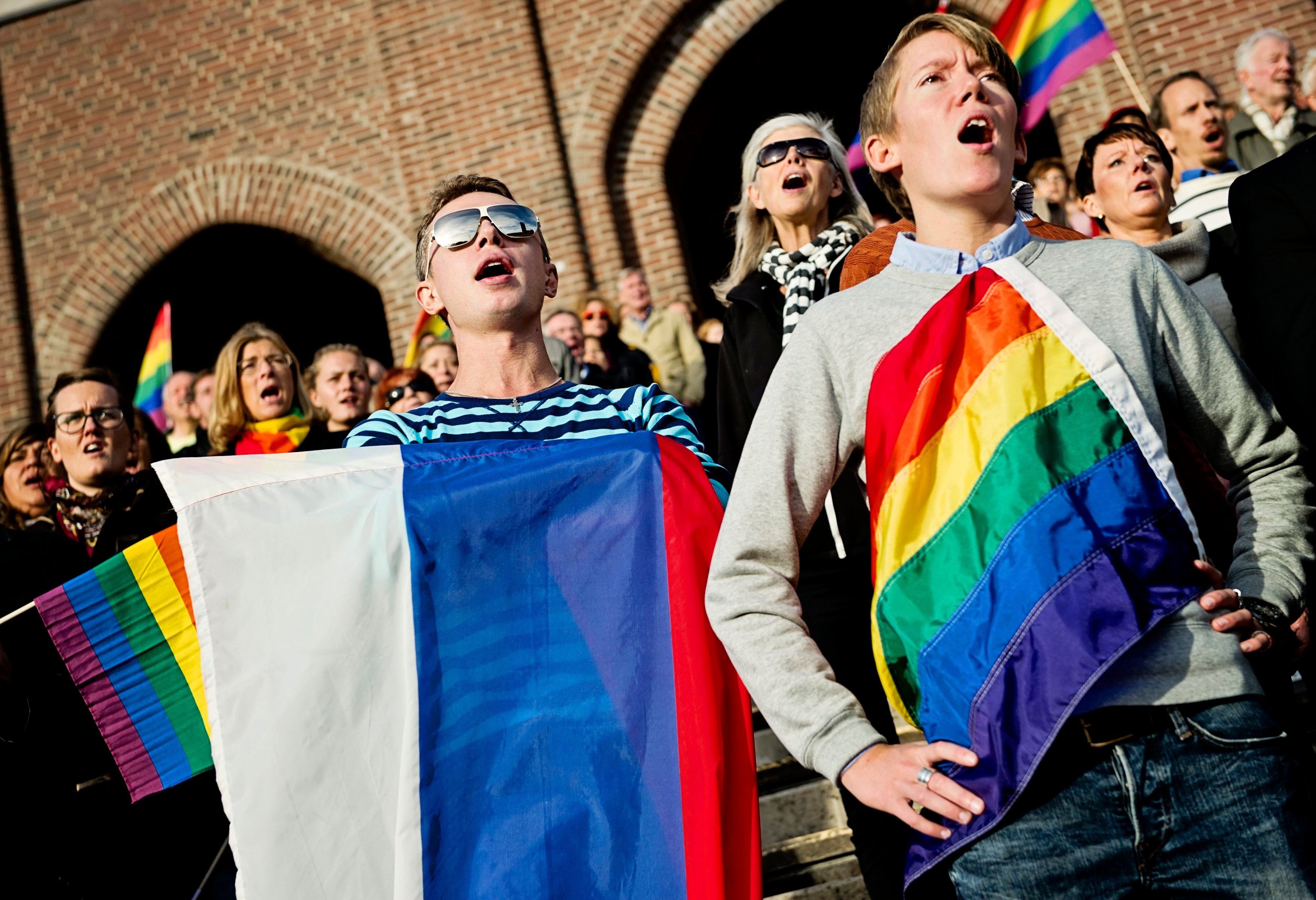 """People sing the Russian national anthem while raising rainbow flags and a Russian flag (C) in solidarity with the lesbian, gay, bisexual and transgender (LGBT) community of Russia, as part of a film project called """"Live and Let Love"""", at the Stockholm Olympic Stadium October 6, 2013. Footage of the crowd singing will be cut together with other musicians from around the world singing the anthem, and the film will be uploaded on YouTube a month ahead of the 2014 Sochi Olympics. Russia has come under fire from activists who argue that a law banning """"gay propaganda"""" bars all gay rights rallies and could be used to prosecute anyone voicing support for homosexuals. REUTERS/Erik Martensson/TT News Agency (SWEDEN - Tags: POLITICS SOCIETY SPORT OLYMPICS) ATTENTION EDITORS - THIS IMAGE WAS PROVIDED BY A THIRD PARTY. FOR EDITORIAL USE ONLY. NOT FOR SALE FOR MARKETING OR ADVERTISING CAMPAIGNS. THIS PICTURE IS DISTRIBUTED EXACTLY AS RECEIVED BY REUTERS, AS A SERVICE TO CLIENTS. SWEDEN OUT. NO COMMERCIAL OR EDITORIAL SALES IN SWEDEN. NO COMMERCIAL SALES"""