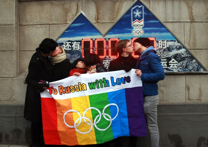 A group of gay and lesbian activists hold a banner of the rainbow flag, the Olympic rings and the words 'To Russia with love'