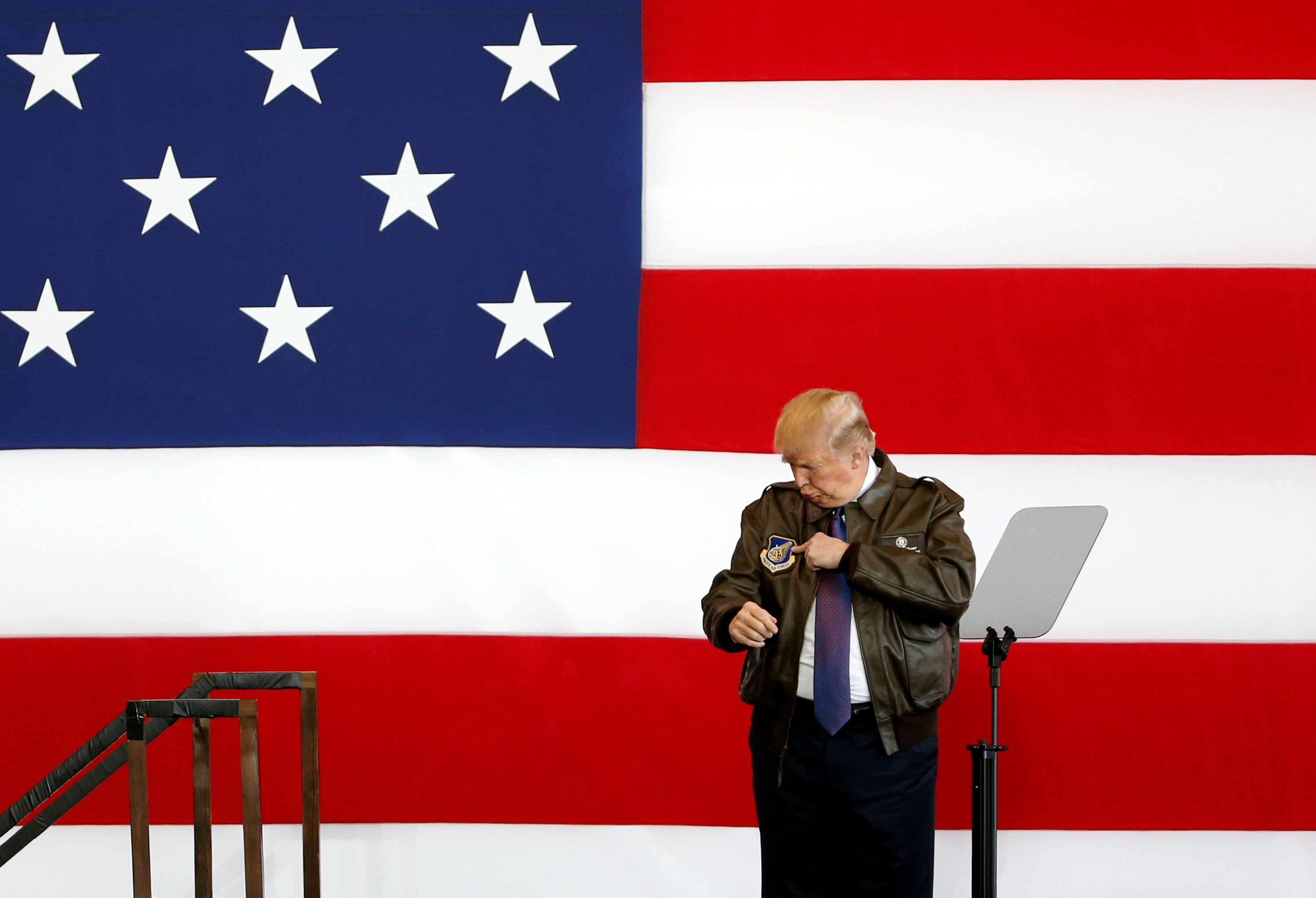 President Donald Trump points to a detail on his flight jacket while on stage at a U.S. Air Force base on the outskirts