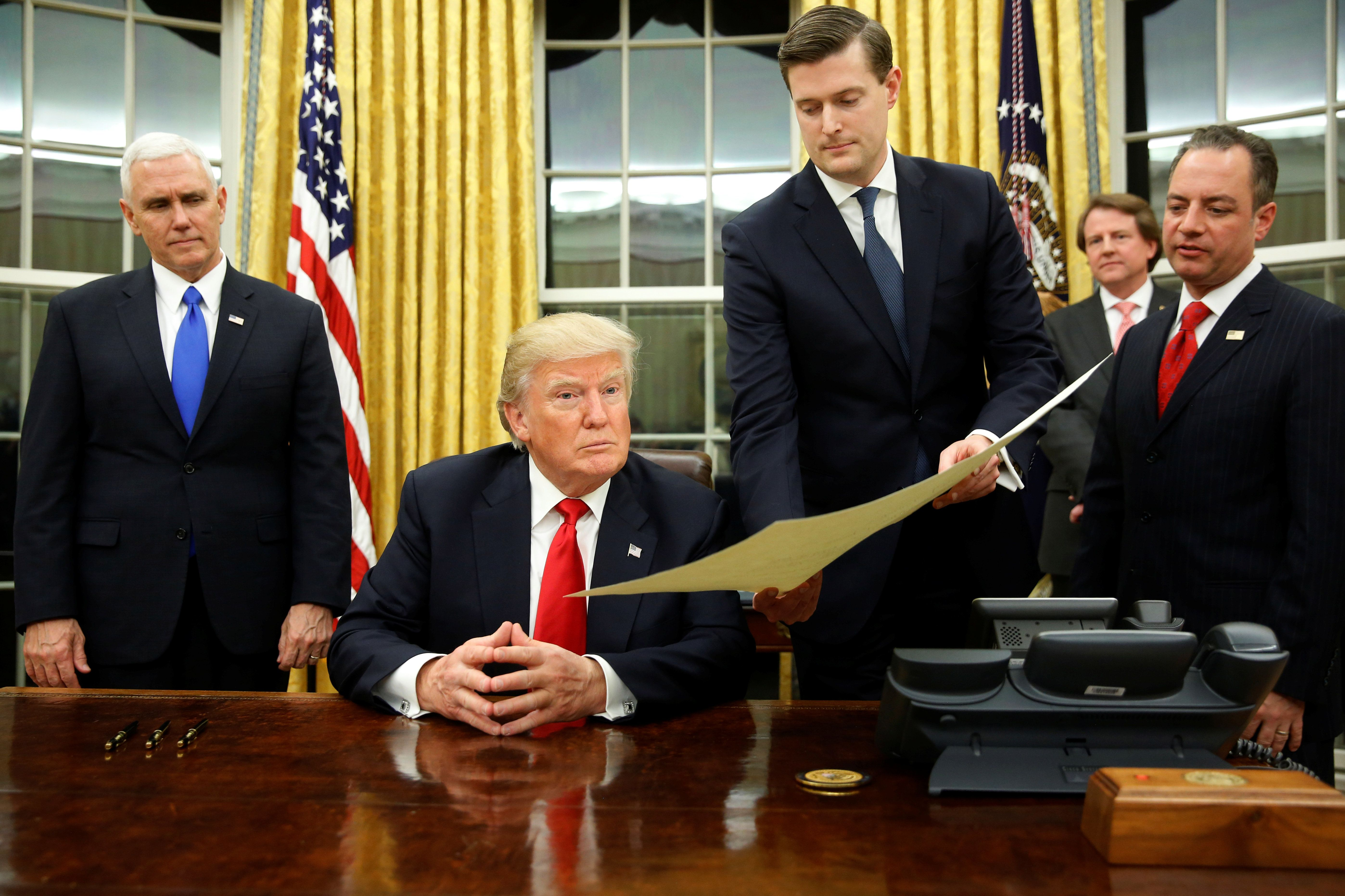 White House Staff Secretary Rob Porter (2nd R) gives U.S. President Donald Trump, flanked by Vice President Mike Pence (L) and Chief of Staff Reince Priebus (R) the document to confirming James Mattis his Secretary of Defense, his first signing in the Oval Office in Washington, U.S. January 20, 2017. REUTERS/Jonathan Ernst
