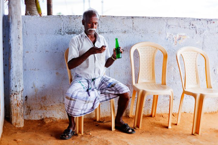 A man chills with a drink and lungi in Tamil Nadu, India.
