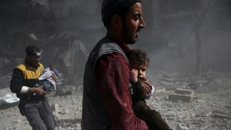 A man holds a child after an airstrike in the besieged town of Douma in eastern Ghouta in Damascus, Syria, February 7, 2018. REUTERS/ Bassam Khabieh