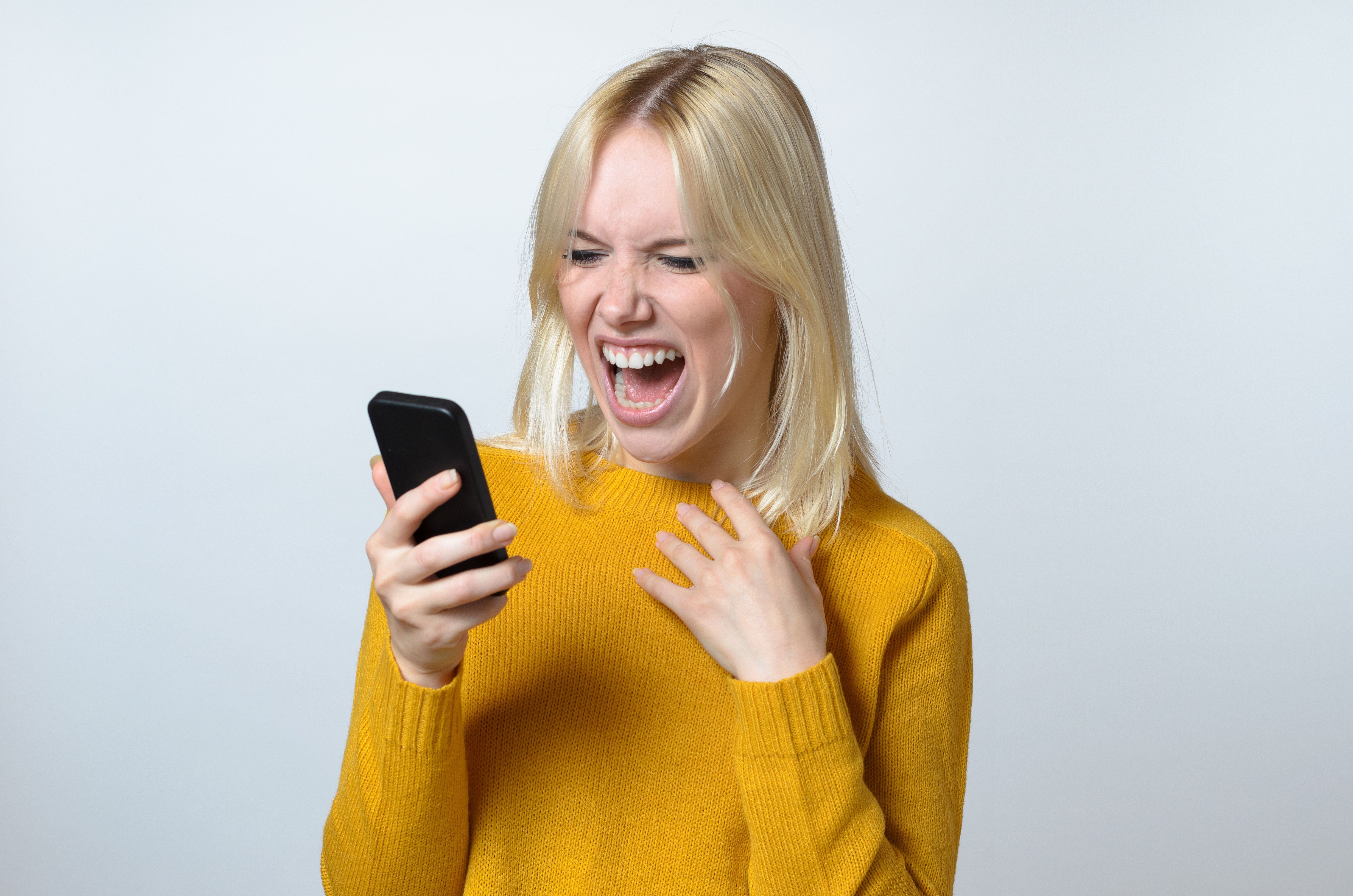 Blond Young Woman Showing Shocked Expression While Looking at her Mobile Phone Against White Background.