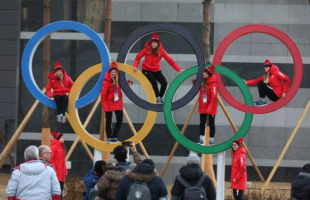 Swiss athletes pose inside the Olympic rings in Pyeongchang, South Korea, on Feb. 8, 2018.