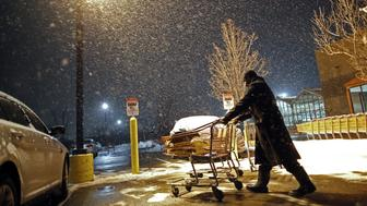 A customer pushes his cart through a parking lot outside a Home Depot Inc. store as snow falls in Evanston, Illinois, U.S., on Thursday, Feb. 8, 2018. The biggest snowstorm of the season is heading towards Chicago. The dump will start late Thursday and continue through the next day, bringing 8 to 10 inches (20 to 25 centimeters). Photographer: Jim Young/Bloomberg via Getty Images