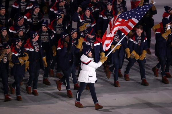 Flag bearer Erin Hamlin of the United States leads her team.