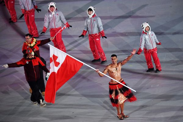 Flag bearer Pita Taufatofua of Tonga and teammates enter the stadium.