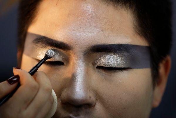 A makeup artist applies glitter to a performer backstage.