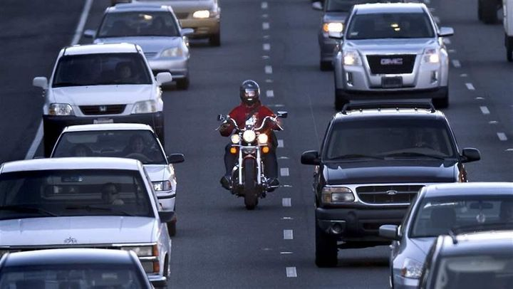 A motorcyclist splits a lane on Highway 99 in Sacramento, California. Other states could follow California in legalizing lane