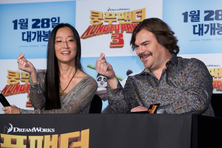 """Kung Fu Panda 3"" director Jennifer Yuh shows actor Jack Black how to form a proper finger heart at a 2016 press ev"
