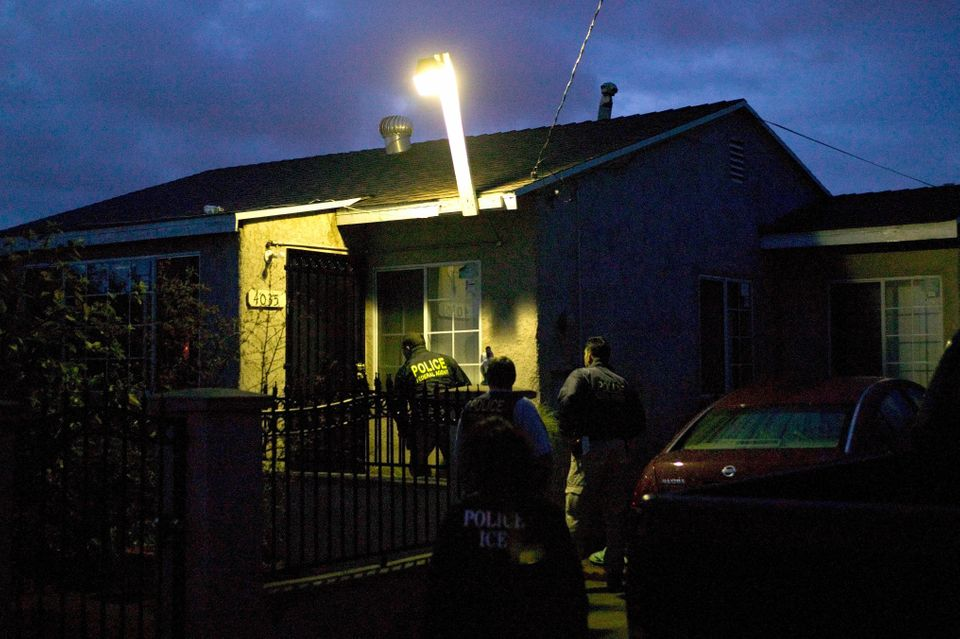 U.S. Immigration and Customs Enforcement agents approach a house in the pre-dawn hours to make an arrest...