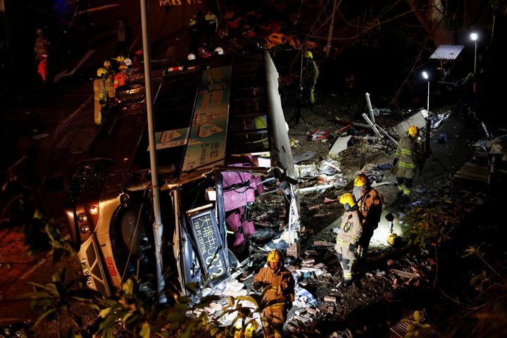 Rescuers walk beside the crashed bus.