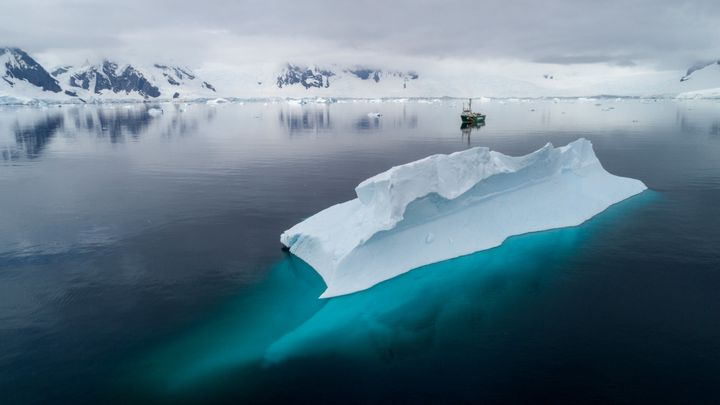 The Greenpeace ship Arctic Sunrise near an iceberg in Charlotte Bay in the Antarctic Ocean.