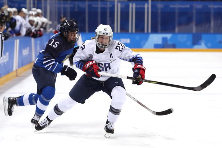 Kacey Bellamy, right, of the United States collides with Finland's Minnamari Tuominen.