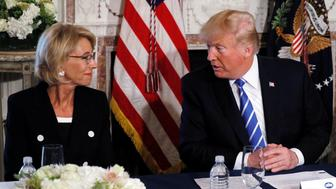 U.S. President Donald Trump turns to Education Secretary Betsy DeVos (L) during his remarks to reporters before a workforce apprenticeship discussion at Trump's golf estate in Bedminster, New Jersey U.S. August 11, 2017.  REUTERS/Jonathan Ernst