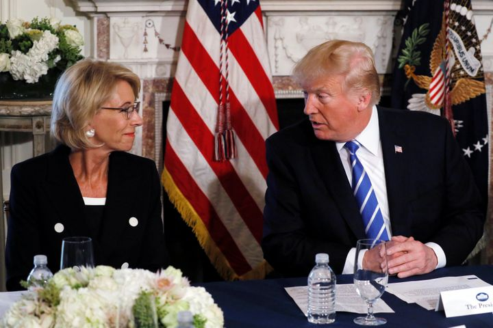 U.S. President Donald Trump turns to Education Secretary Betsy DeVos (L) during his remarks to reporters before a workforce a