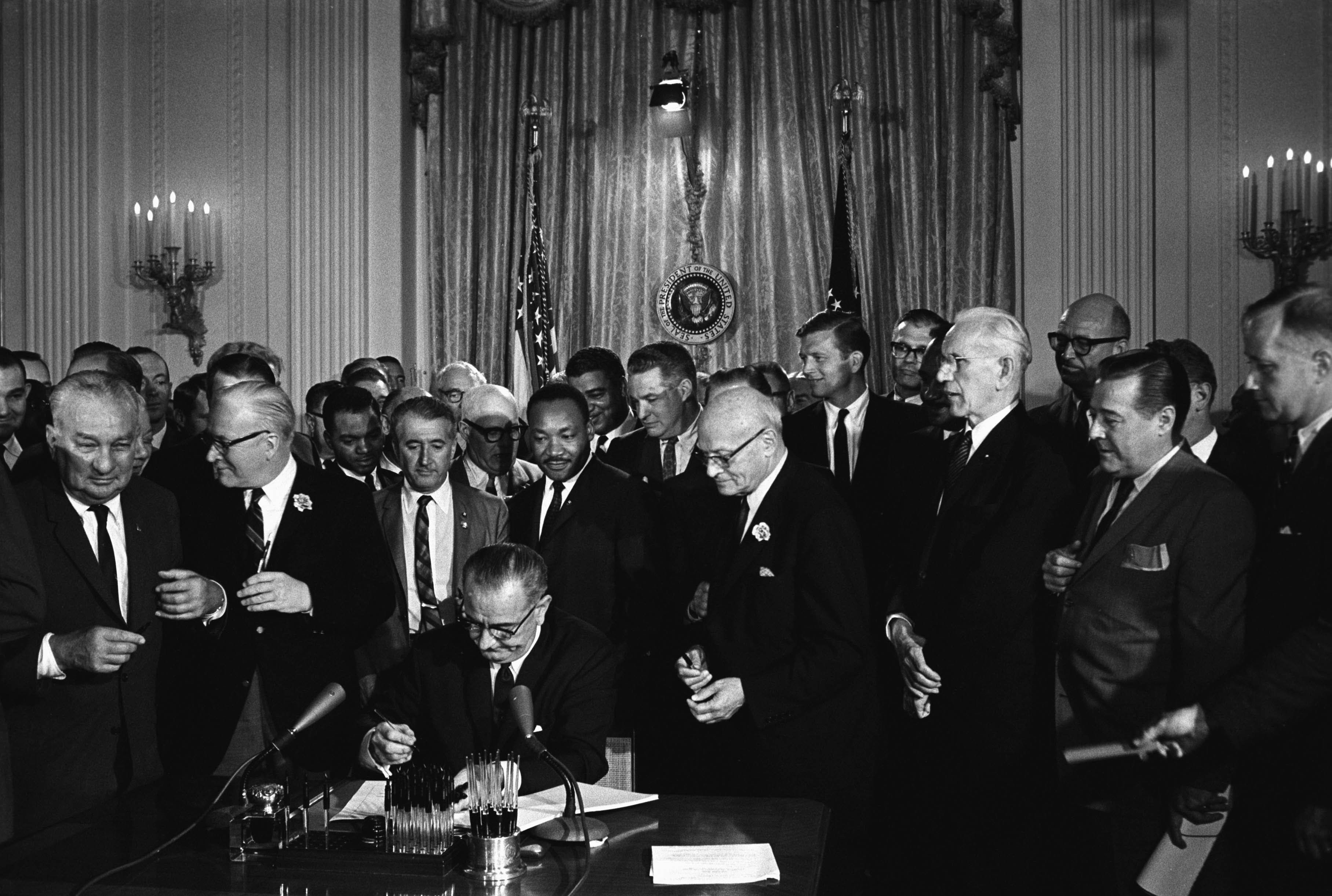 Then-President Lyndon B. Johnson signs the 1964 Civil Rights Act, which established a Justice Department office to provi