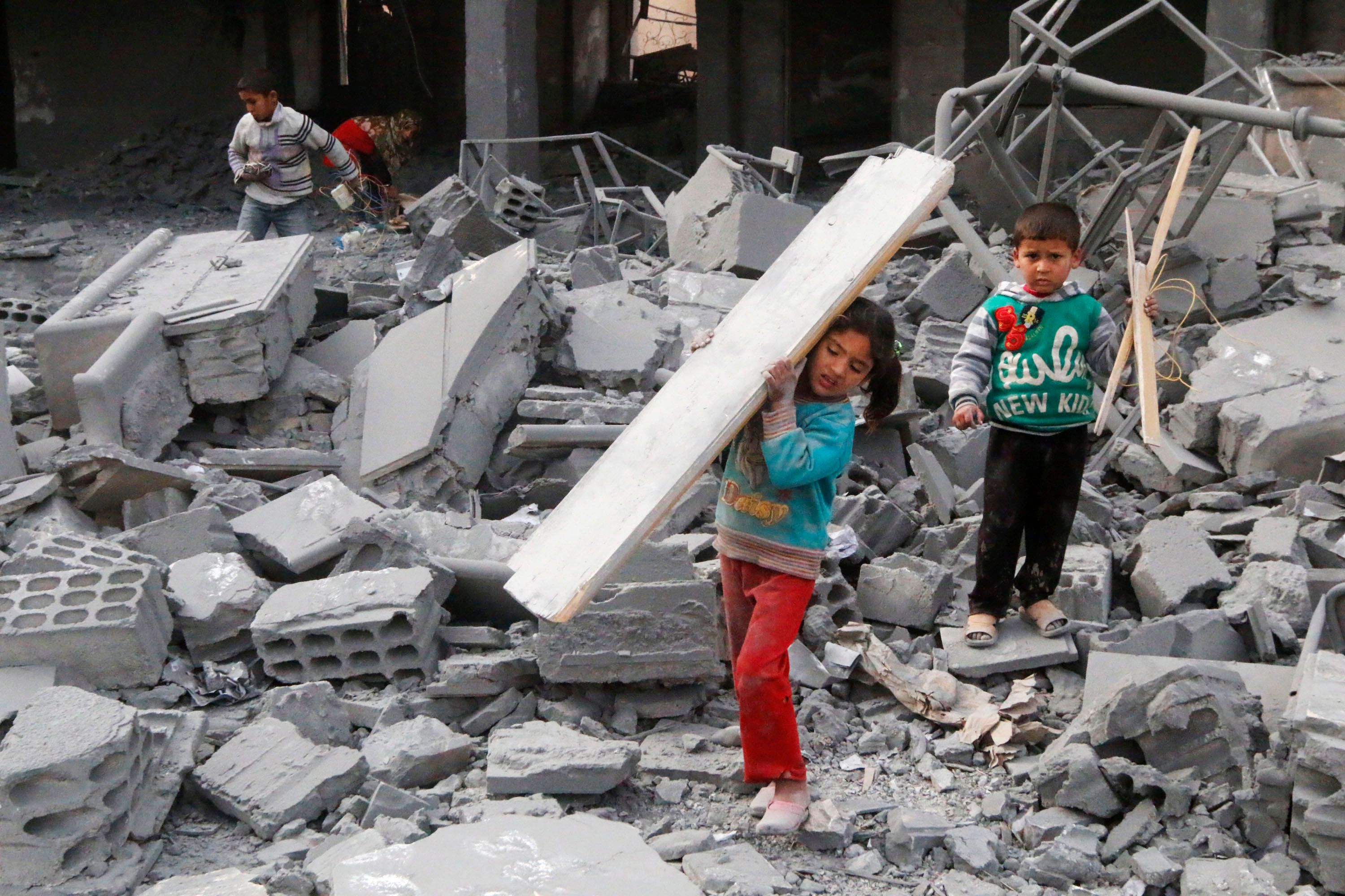 Children collect items from the debris of a school destroyed in what activists said were overnight U.S.-led airstrikes agains