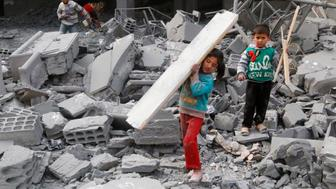 Children collect items from among the debris of a school for the deaf and mute, destroyed in what activists said were overnight U.S.-led air strikes against the Islamic State, in Raqqa November 24, 2014.  Raqqa, in eastern Syria, is controlled by the Islamic State. The United States and its allies have conducted two dozen strikes against Islamic State militants since Friday, launching nine strikes in Syria and 15 strikes in Iraq, according to U.S. Central Command. REUTERS/Nour Fourat  (SYRIA - Tags: POLITICS CIVIL UNREST CONFLICT)