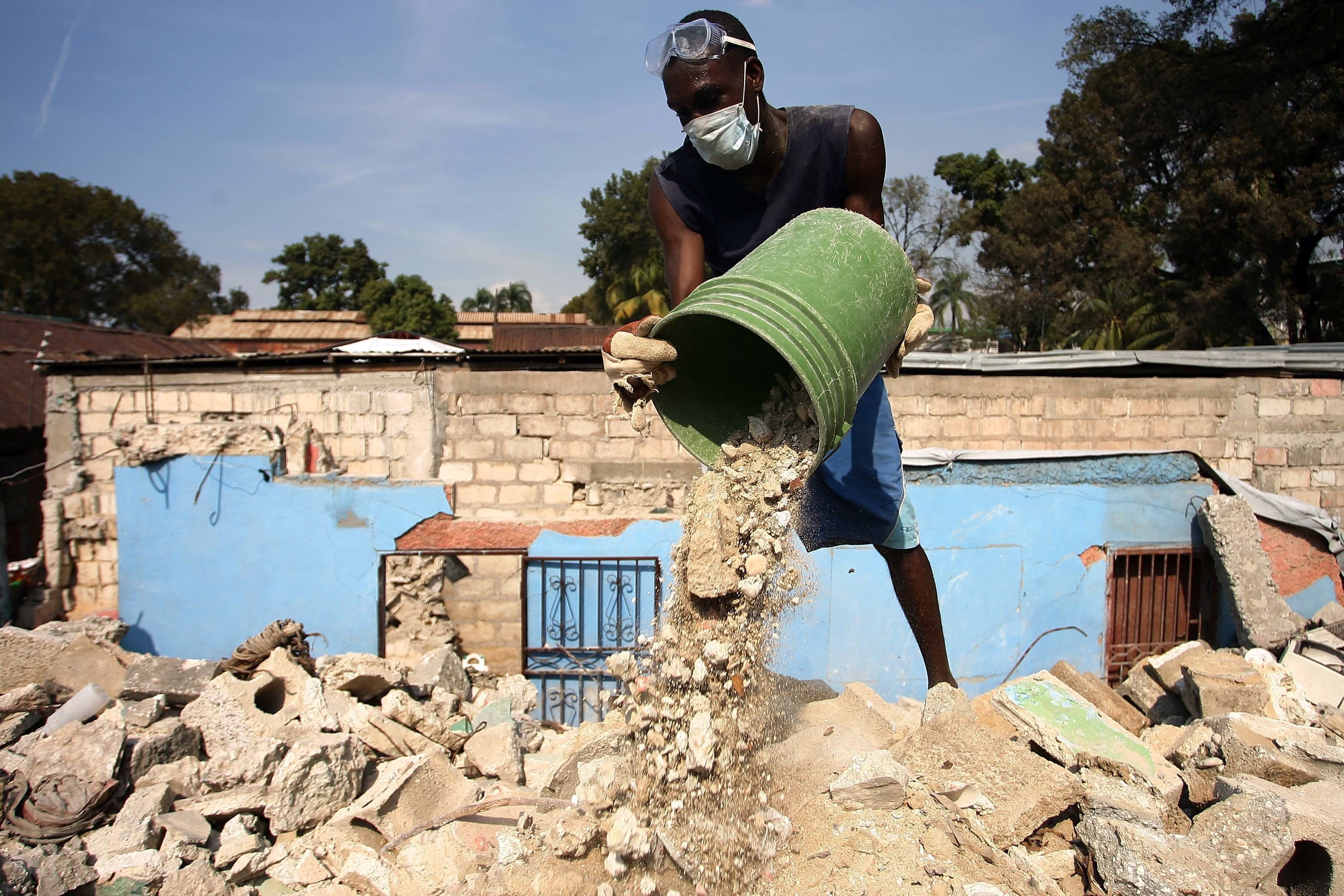 Haitians clean up the debris in a house that was destroyed in the last earthquake of 2010.