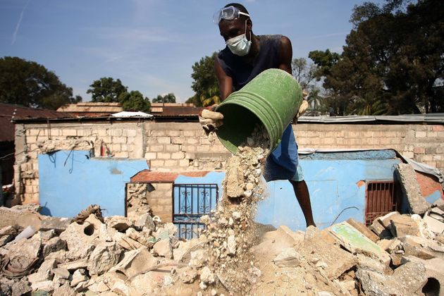 Haitians clean up the debris in a house that was destroyed in the last earthquake of