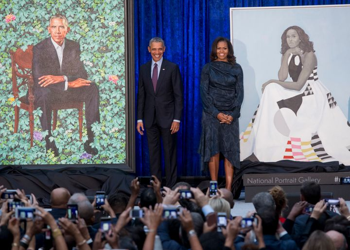Barack and Michelle Obama with their portraits.