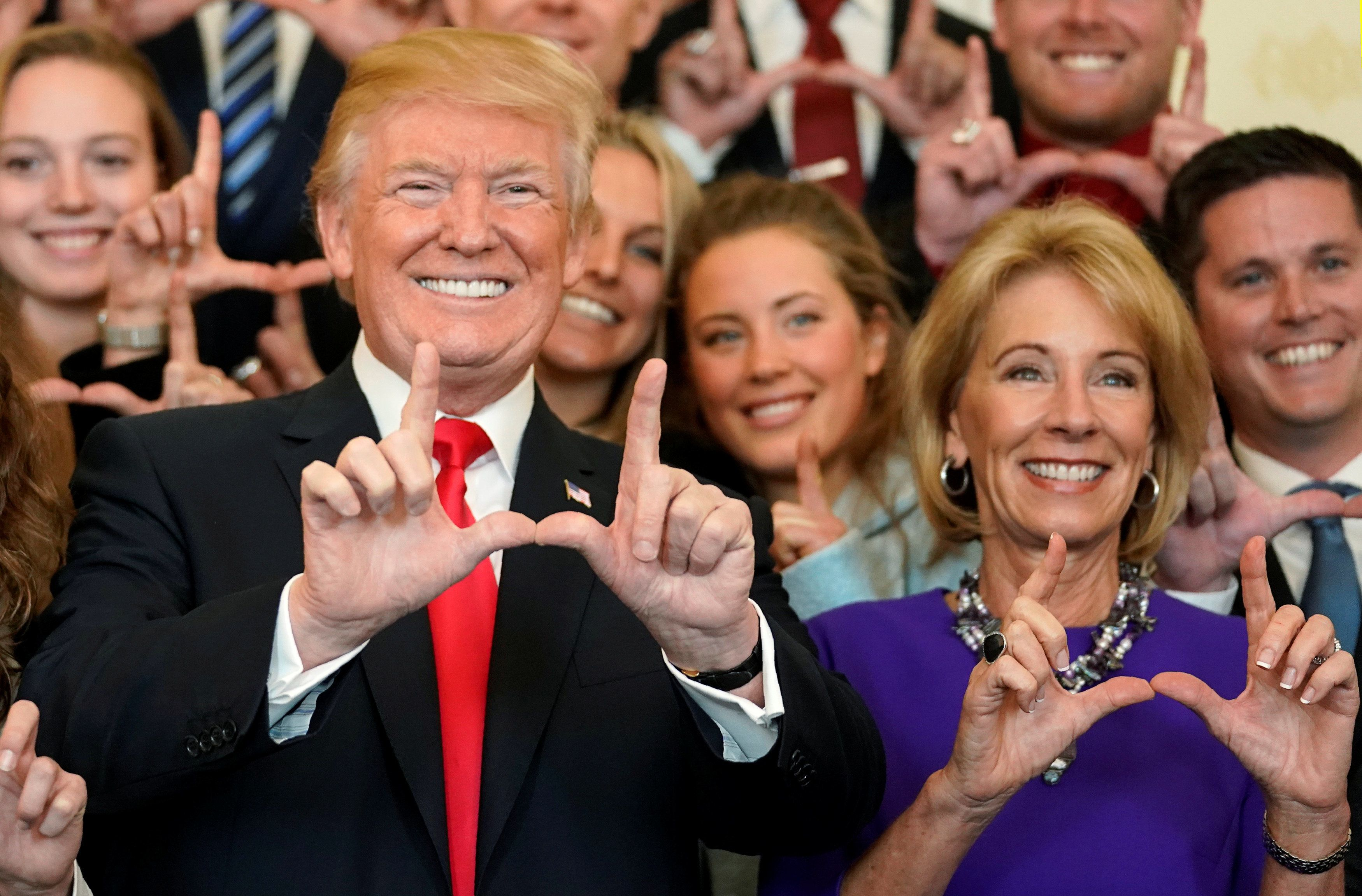 """President Donald Trump and Education Secretary Betsy DeVos make """"U"""" symbols with their hands while posing with the Utah Skiin"""