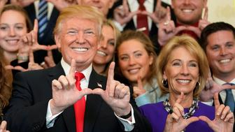 "U.S. President Donald Trump and Education Secretary Betsy DeVos make ""U"" symbols with their hands while posing with the Utah Skiing team as they greet members of Championship NCAA teams at the White House in Washington, U.S., November 17, 2017.   REUTERS/Joshua Roberts"