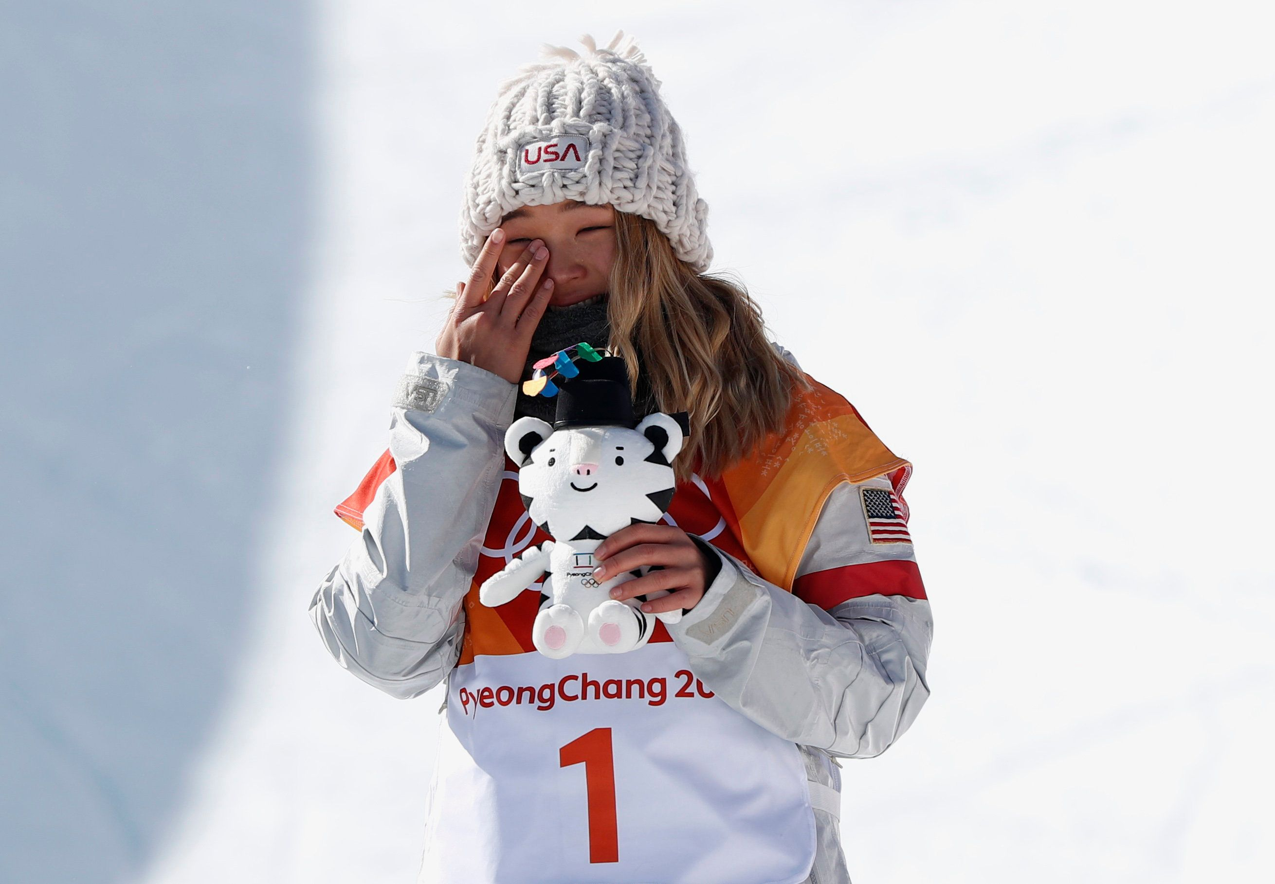 Snowboarding - Pyeongchang 2018 Winter Olympics - Women's Halfpipe Finals - Phoenix Snow Park - Pyeongchang, South Korea - February 13, 2018  - Gold medallist Chloe Kim of the U.S. reacts while holding her Soohorang Olympic mascot during the flowers ceremony. REUTERS/Issei Kato