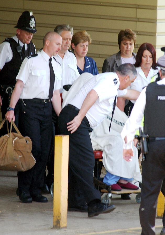Huntley, hidden under a blanket and wearing blue pyjamas and red slippers is escorted from hospital to...