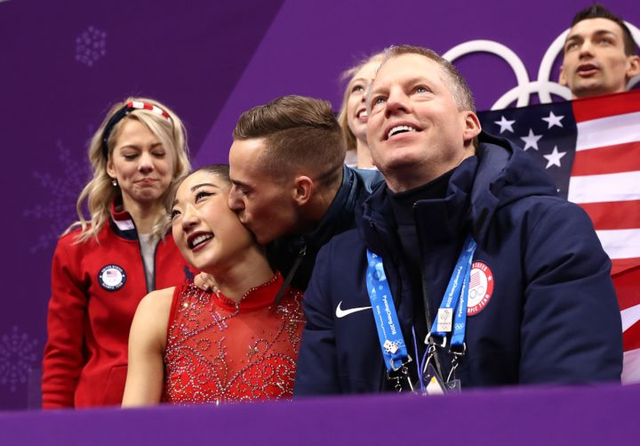 Mirai Nagasu is kissed on the cheek by teammate Adam Rippon.