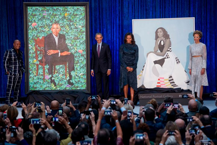 The crowd takes their own pictures of Kehinde Wiley, Barack Obama, Michelle Obama, Amy Sherald and the two portraits.