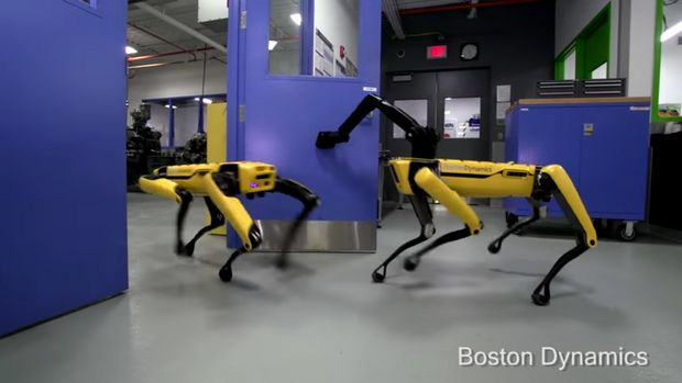 A Boston Dynamics robot called SpotMini is seen opening the door for a fellow robot
