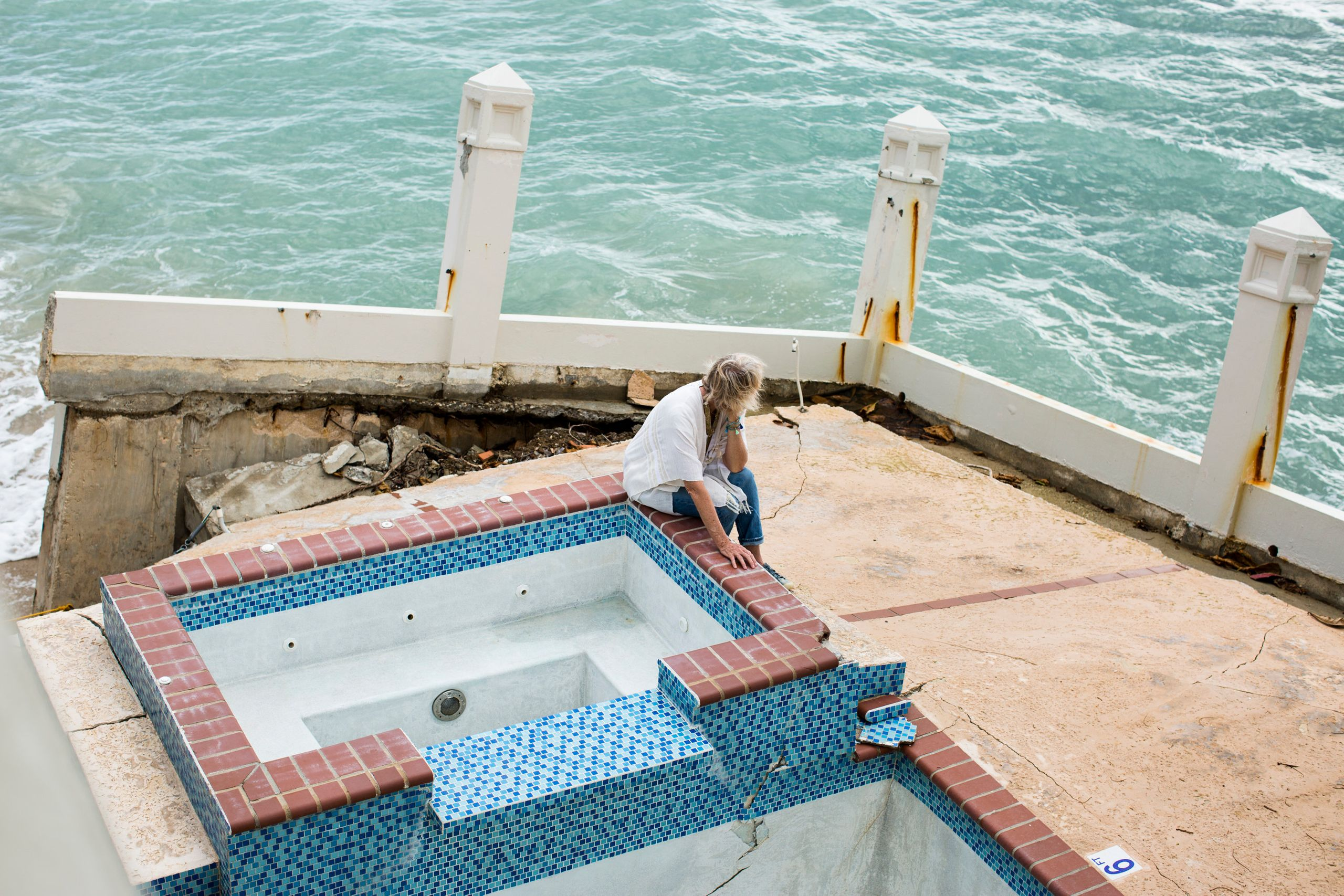Lisa Brown Masters, owner of Tres Sirenas Beach Inn, sits on her hotel's front porch, broken by the hurricane